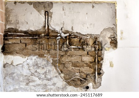 Damaged wall plumbing in a house closeup - stock photo