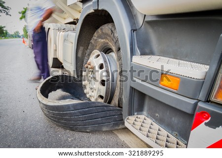 Damaged 18 wheeler semi truck burst tires by highway street, with blurred driver. - stock photo