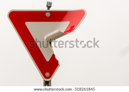 Damaged yield sign against a cloudy winter sky. The curled back is scratched and dirty; lines that reflect headlights back in the same direction can be seen under the diamond pattern on the front. - stock photo