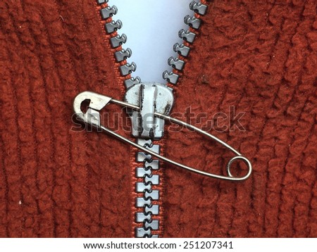 Damaged zipper repaired with safety pin close up horizontal      - stock photo