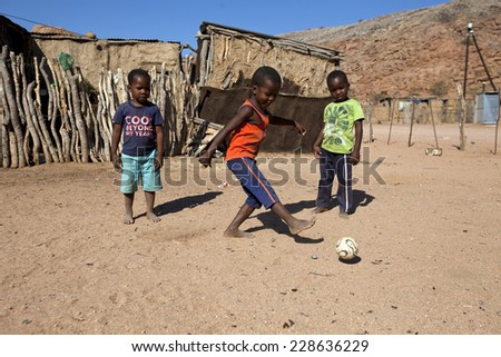 DAMARALAND, NAMIBIA - JUNE 23: Unidentified african boys play football in Damaraland village on 23 of June 2013 in Namibia, South Africa - stock photo