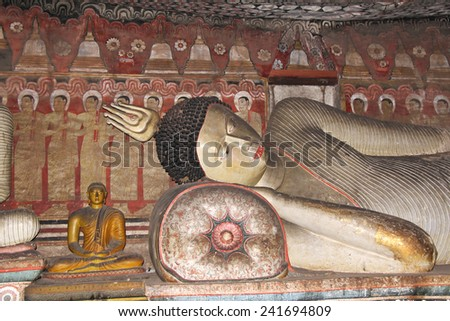 DAMBULLA, SRI LANKA-DEC.3,2014:  Reclining Buddha in the best preserved and largest cave complex in the country and a UNESCO site.  Hundreds of Buddhas are found in the series of cave complexes. - stock photo