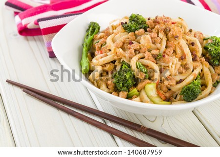 Dan Dan Noodles - Chinese noodles with minced pork and sprouting broccoli in a fragrant spicy sauce. Sichuan cuisine. - stock photo