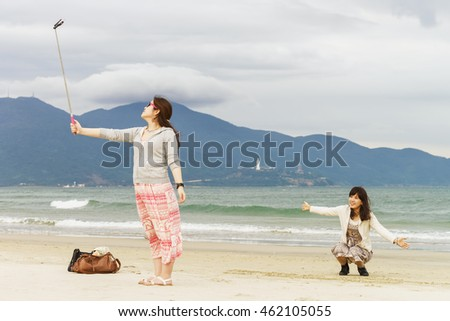 Danang, Vietnam - February 20, 2016: Young girls making a selfie with selfie stick in the China Beach in Danang in Vietnam