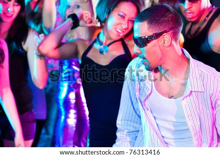Dance action in a disco club - group of friends, men and women of different ethnicity, dancing to the music having lots of fun - stock photo