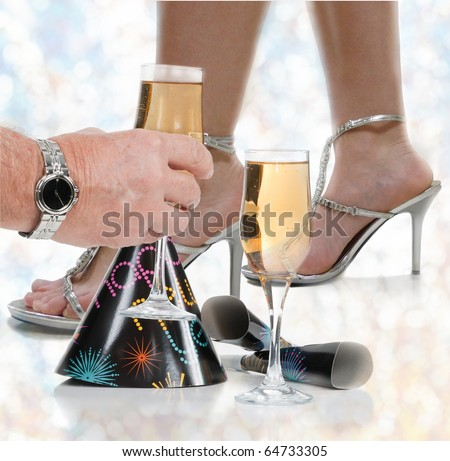 Dance floor ground view on New Year's Eve with a couple's party favorites; glasses of champagne, one glass being lifted just before midnight, a girl in high heels with party lights in the background. - stock photo