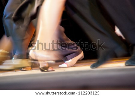 Dance moves and motion on salsa class. Milonga dance club - dancers performing an Argentinian tango. - stock photo