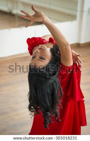 dancer dressed in red rehearsing in studio - stock photo