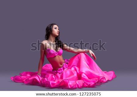 dancer in oriental pink costume sitting on floor - stock photo