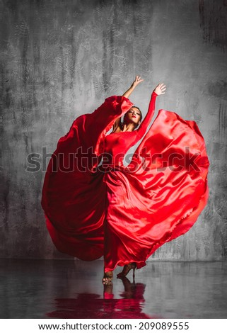 dancer in red dress posing on studio background - stock photo