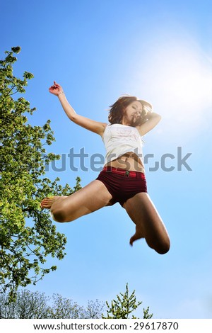 dancer jumping behind blue sky - stock photo