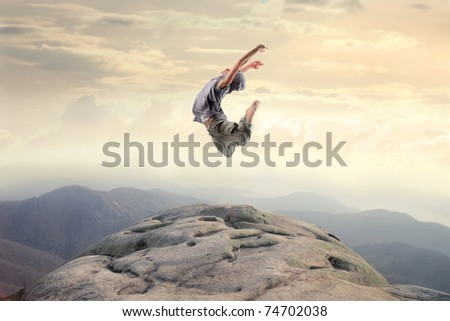 Dancer jumping on a rock - stock photo