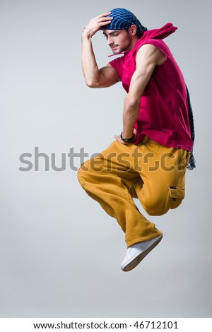 Dancer jumping over gray background, studio shot - stock photo