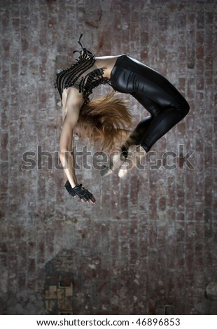 dancer makes a difficult jump  agains brick wall