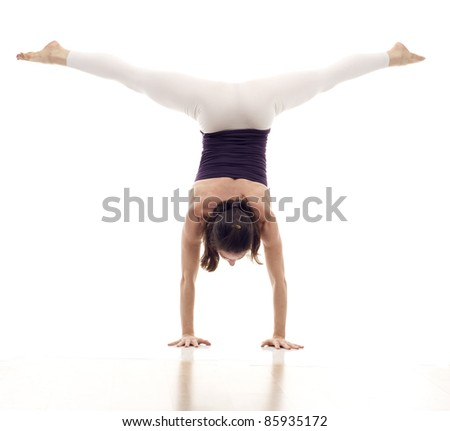 Dancer standing on hands, holding legs in air isolated  over white background - stock photo