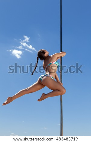 dancer with pigtail performs acrobatic on pole against blue sky