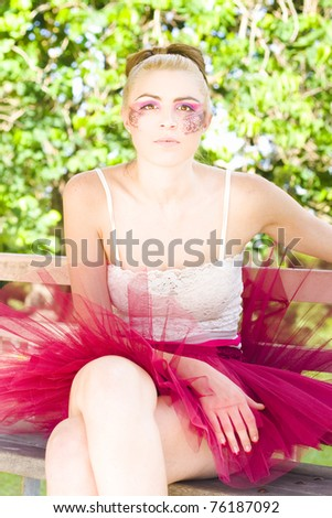 Dancer Woman Wearing A Pink Leotard And Glamour Cosmetics Has A Creative Insight And Vision While Sitting Down On A Chair Outdoors - stock photo