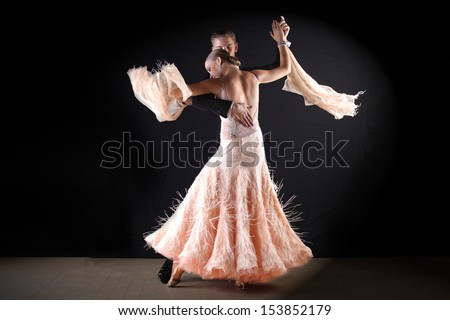 dancers in ballroom against black background