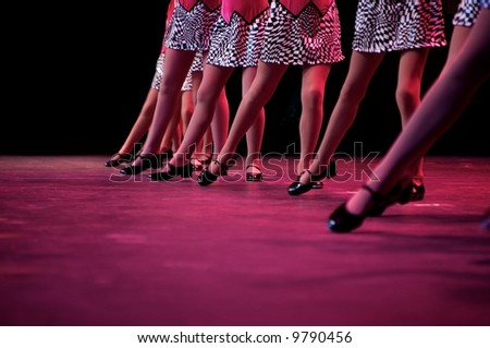 Dancers on stage during a recital in bright costumes. Noise reduction was applied on the floor and the dancers in the background but not the foreground dancers. - stock photo