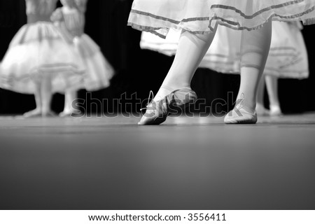 Dancers on stage during a recital. Originally shot in Black and White. Noise reduction was applied on the floor and the dancers in the background but not the foreground dancer. - stock photo