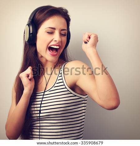 Dancing active young woman in headphones singing the song. Vintage portrait - stock photo