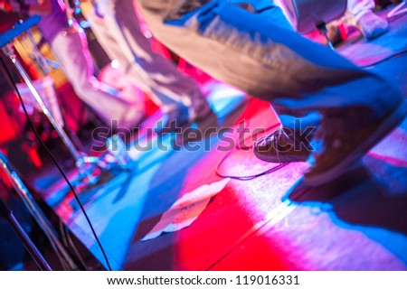 Dancing at a party with red and blue lights - stock photo