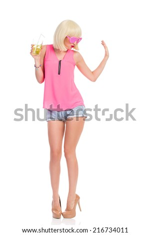 Dancing at the party. Carefree blonde young woman in high heels, pink top and jeans shorts dancing with lime drink and waving hand. Full length studio shot isolated on white. - stock photo
