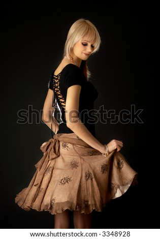 dancing blond in brown skirt over black background - stock photo