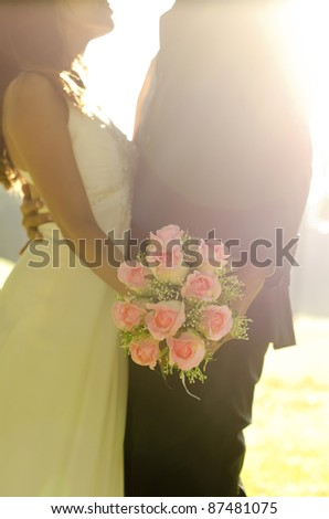Dancing bride and groom with bouquet in hand - stock photo