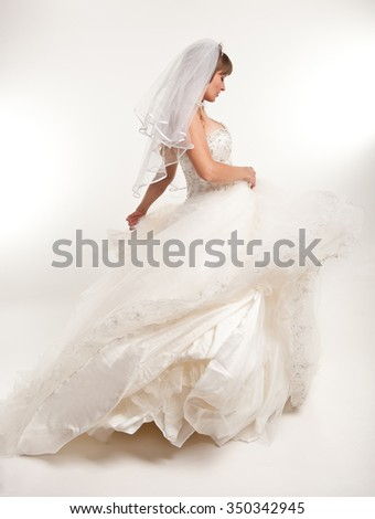 Dancing bride in a white dress on a white background