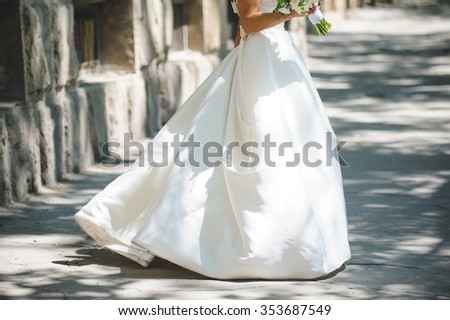 dancing bride in long dress in street - stock photo