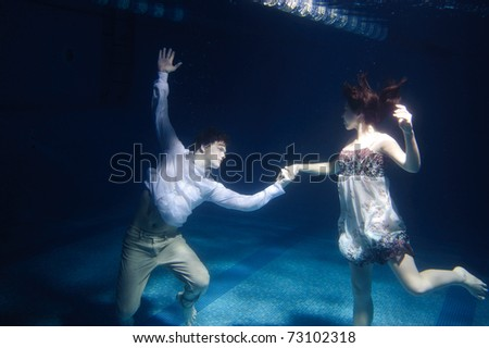 Dancing couple under water in swimming pool - stock photo