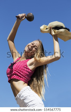 Dancing girl holding maracas and hat in hands