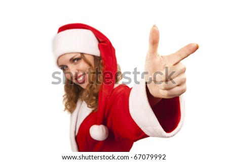Dancing girl in santa suit is pointing her finger at the camera and looking with a smile. Isolated on white. (Focus on finger) - stock photo