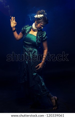 Dancing girl on dark background with smoke.
