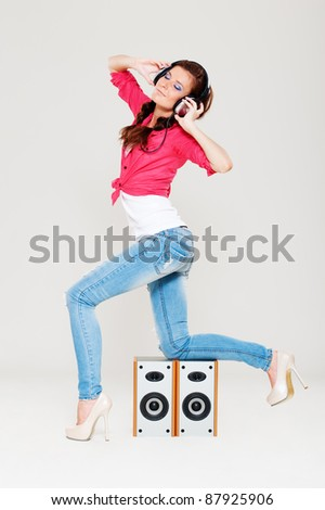 dancing girl with headphones on her head posing near speakers - stock photo