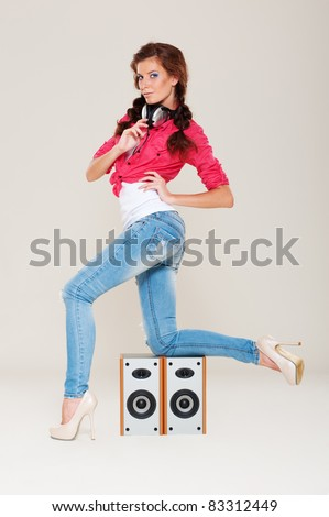 dancing girl with headphones on her neck posing near speakers - stock photo