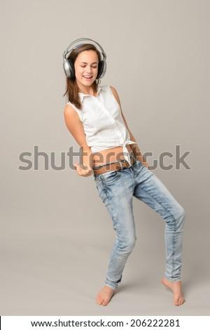 Dancing girl with headphones singing enjoy music full length on gray - stock photo