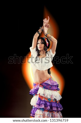 Dancing Gypsy girl with tongue of flame on black background - stock photo
