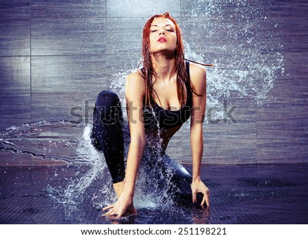 Dancing is her passion. Portrait of beautiful young contemporary dancer dancing under the water shower while standing against black background - stock photo