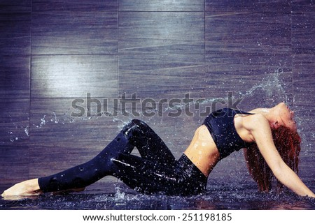 Dancing is her passion. Side view of beautiful young contemporary dancer dancing under the water shower while standing against black background - stock photo