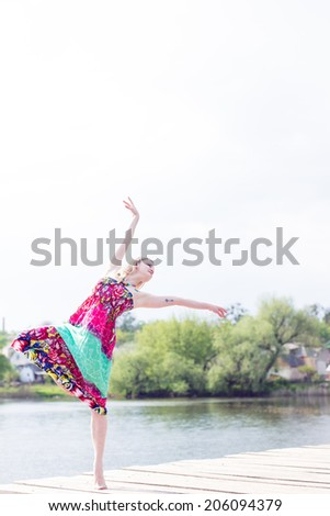 dancing joy: posing beautiful blond young slim woman enjoying stretching in long light dress at water lake on summer green outdoors & white sky copy space background portrait image - stock photo