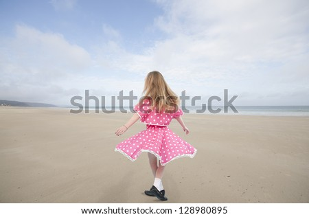 Dancing little girl in pink dress, at the beach - stock photo