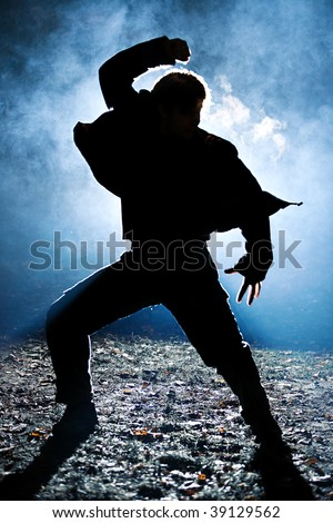 Dancing man silhouette. Bright light flash behind. - stock photo