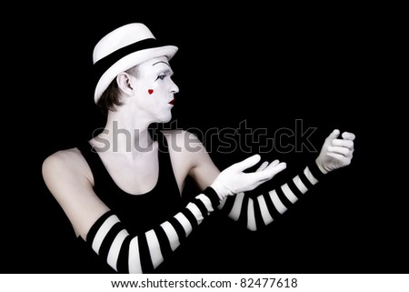 dancing mime in white hat with  heart on her cheek on black background - stock photo