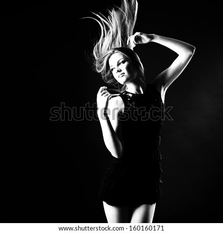 Dancing party girl. Young beautiful excited woman listening music and dancing with long blond hair fly-away, b&w - stock photo