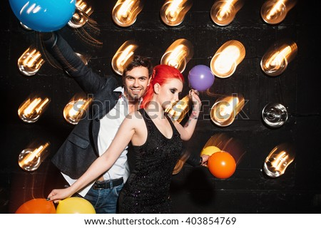 Dancing  people celebrate in night club. Laughing people dancing and  have fun on the weekend at nighttime.  They express their feelings openly. - stock photo