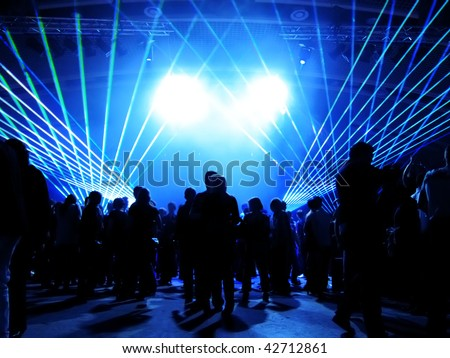 Dancing people in a disco in front of blue laser lights - stock photo