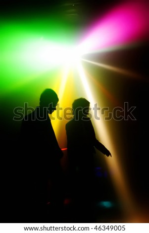 Dancing people in a disco in front of colorfull disco-lights - stock photo