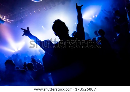 Dancing people in a disco raising their arms - stock photo